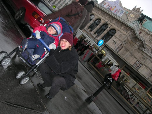 """My wife and son hard at work researching MOZART'S LAST ARIA at the coldest time of the year in Vienna. Behind them is the Staatsoper, the State Opera House, which wasn't there when Mozart was around. I saw a perfect production of """"The Magic Flute"""" there."""
